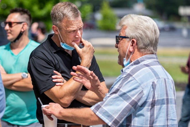 U.S. Rep. Scott Perry, left, R-Pa., speaks to Nick Loxas, owner of the Boomerang Comedy Zone, before a rally against Gov. Wolf's new COVID-19 restrictions in restaurants and bars, Friday, July 17, 2020, outside of the Bonefish Grill in Lower Allen Township, Pa. (Joe Hermitt/The Patriot-News via AP)