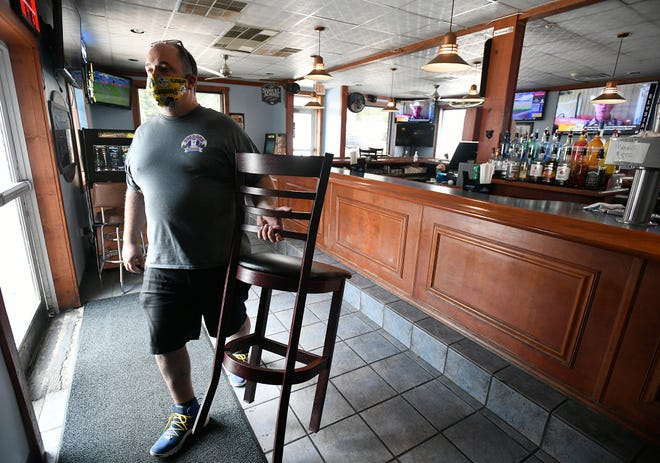 BigDogz Grill owner Michael Ziants removes the last chair from his bar  in Johnstown, Pa. to comply with Governor's Wolf new COVID-19 restrictions for bars on Thursday, July 16, 2020.  (Todd Berkey/The Tribune-Democrat via AP)