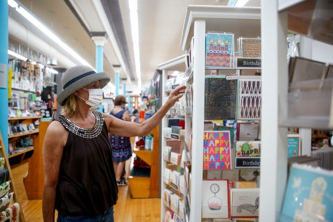 Renee Holman looks through the card section at Zandbroz Variety on Saturday, July 18, 2020 in Sioux Falls, S.D. The store has required customers to wear masks to prevent the spread of COVID-19.
