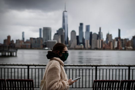 In this April 10, 2020 file photo a woman wearing a face mask walks along the Jersey City waterfront with the New York City skyline in the background.
