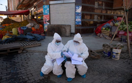 Healthcare workers dressed in full protective gear organize their documents of data they have collected during a house-to-house new coronavirus testing drive, ringed by a produce market in the Villa Dolores neighborhood of El Alto, Bolivia, Saturday, July 18, 2020.