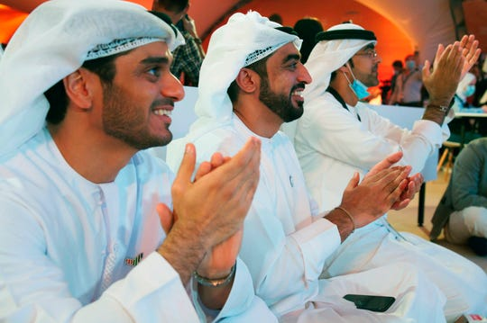 "Emirati men claps as they watch the launch of the ""Amal"" or ""Hope"" space probe at the Mohammed bin Rashid Space Center in Dubai, United Arab Emirates, Monday."