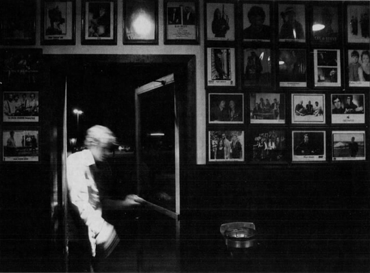 A patron enters through the side door past a wall of publicity photos of various musicians at The Mill Restaurant, June 19, 2003.