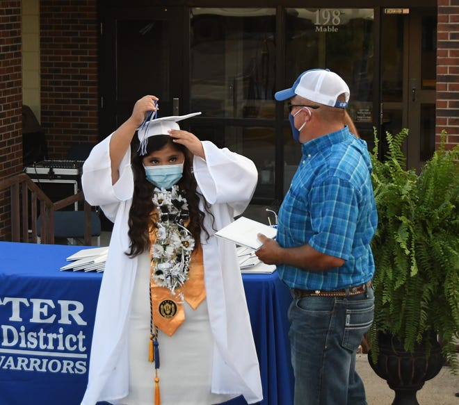 A 2020 graduate moves her tassel to the other side of her mortarboard Saturday evening during the Cotter School District's graduation ceremony.