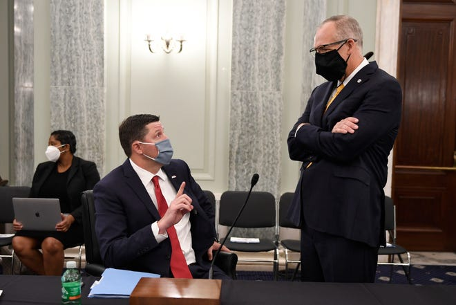 SEC commissioner Greg Sankey (right) talks with Ole Miss vice chancellor for intercollegiate athletics Keith Carter (left) before they testify at a Senate Commerce Committee hearing on Capitol Hill in Washington in July.