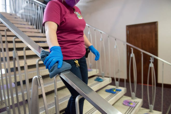 A member of the Legislative janitorial crew cleans a railing inside the Legislature on the eleventh day of the 31st Special Session in Carson City on Saturday, July 18, 2020.