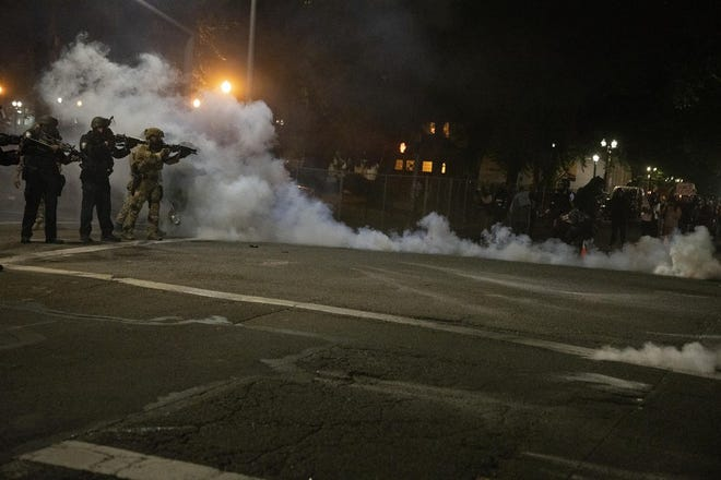 Federal law enforcement officers fire impact munitions and tear gas at protesters demonstrating against racism and police violence in front of the Mark O. Hatfield federal courthouse in Portland, Oregon, on July 16, 2020.