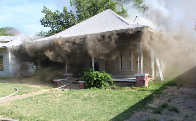 Wichita Falls firefighters work the scene of a house fire Sunday morning on Tenth Street
