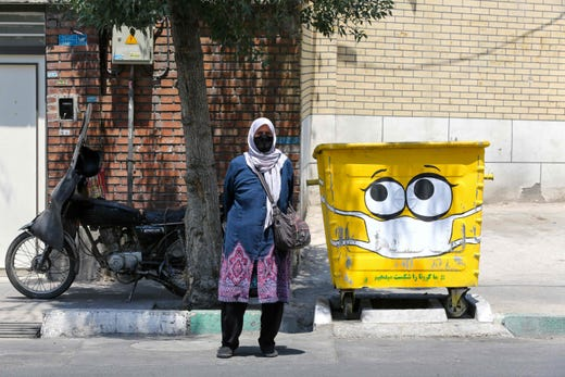 An Iranian woman stands next to a street bin, painted with a drawing of a mask in a campaign to spread awareness over the COVID-19 coronavirus pandemic in the capital Tehran on July 18, 2020. P resident Hassan Rouhani said that 35 million Iranians may contract the coronavirus, as the country still did not have herd immunity although a quarter of the population may be infected.
