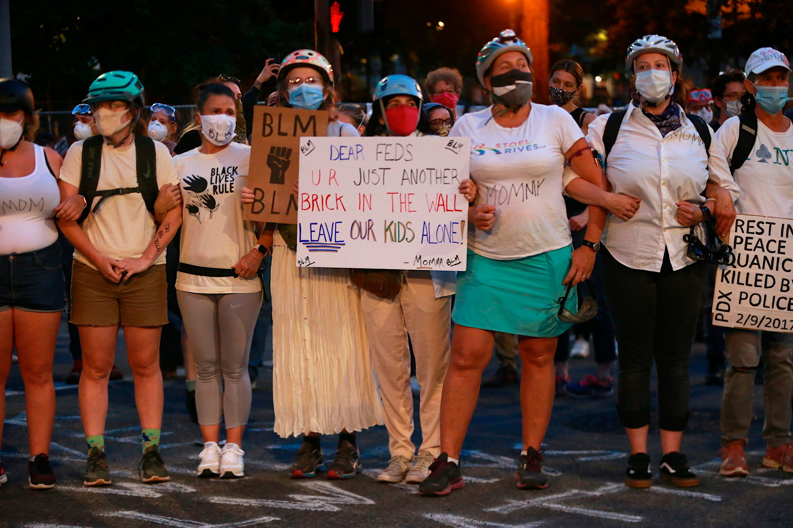 Mothers stand arm-in-arm outside the Justice Center in downtown Portland, Oregon, on July 18 during another night of protests. Activists and lawmakers expressed outrage over accusations that federal agents circulating in unmarked cars grabbed protesters off the streets.