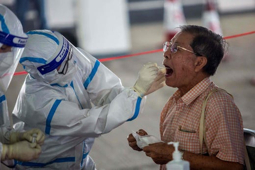 A taxi driver gets tested by health workers for coronavirus COVID-19 at a makeshift testing station in a carpark in Hong Kong on July 19, 2020. The deadly coronavirus is spreading out of control in Hong Kong with a record 100 new cases confirmed, the finance hub's leader said as she tightened social distancing measures to tackle the sudden surge in infections.