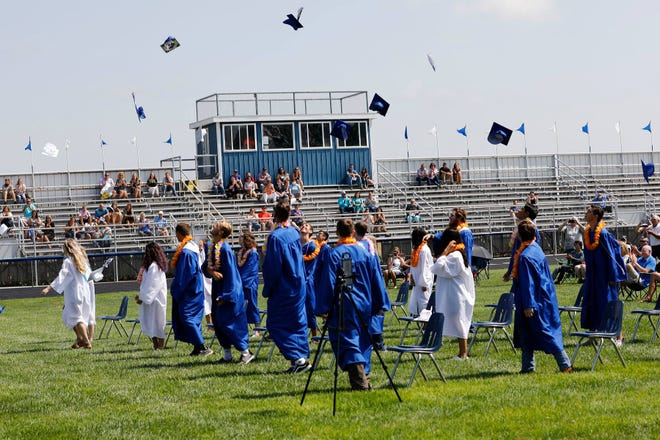 "Mortarboards of the 2020 St. John High School graduating class fill the air at the conclusion of their outdoor graduation ceremony, Saturday, July 11, at the St. John High Football field. Several students decorated their caps with unique designs special to them, including one with a  verse from Isaiah reading ""Where God guides, He provides."""