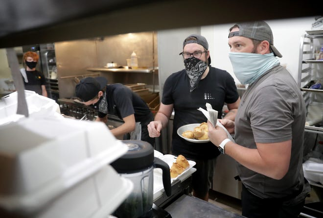 Author's Kitchen + Bar co-owners Matias Whittingslow, left, and Josh Sickler, right, work with Brian Gabronski, center, to prepare empanadas for curbside pick up.