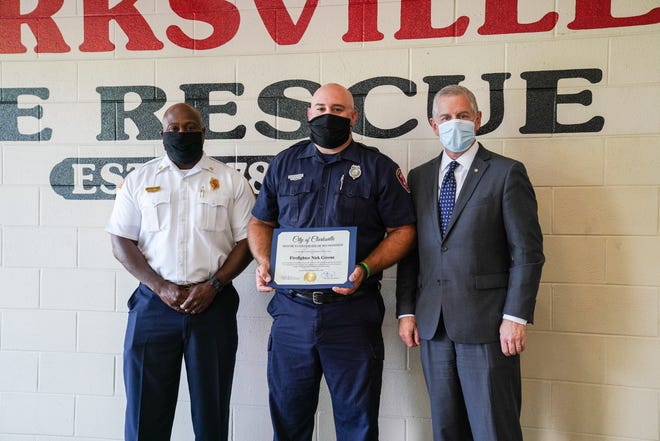 Fire Chief Freddie Montgomery, left, and Mayor Joe Pitts, right, presented Firefighter Nick Greene with a Mayor's Certificate of Recognition on Monday in honor of his quick actions to save a man and his pets from a house fire.