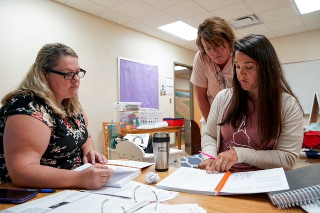 (From L to R) Dani Warren, Trina Snider, and Casey Murphy, all pre-k teachers, look over lesson plans with one another at Chapel Hill School's temporary location in First Baptist Church in Clarksville, Tenn., on Monday, July 13, 2020.