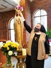 Sister Rosanne Marie Glaza crowns the statue of Our Lady on May 1 during a ceremony at the Presentation of the Blessed Virgin Mary Convent in Livonia.