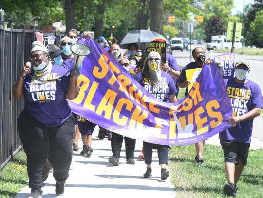 Fifty plus protestors march to a Service Employees International Union Healthcare Michigan rally in front of Hartford Nursing and Rehabilitation Center in Detroit on Monday.