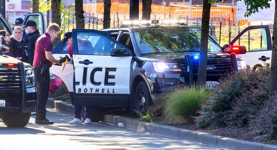 Law enforcement investigators examine the scene a day after one police officer was killed and another was injured in a July 13, 2020, shooting in downtown Bothell, Washington.