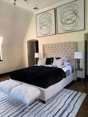 A master bedroom is given a loftlike feel through the use of a tall headboard and oversized artwork.