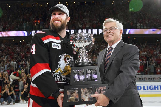 AHL commissioner Dave Andrews, right, presents the Calder Cup to Grand Rapids captain Nathan Paetsch in 2017.