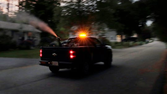 A crew from the East Middlesex Mosquito Control Project spray to control mosquitos from a pick-up truck on Wednesday, July 8, 2020, while driving through a neighborhood in Burlington, Mass.