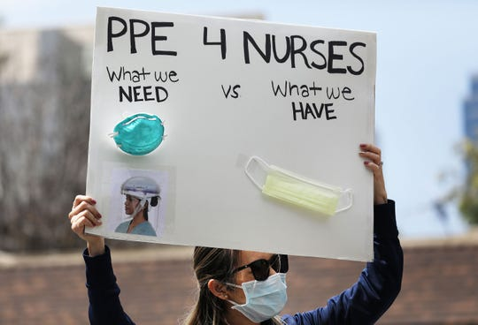 A nurse holds up a sign to protest the lack of personal protective gear available at UCI Medical Center amid the coronavirus pandemic on April 3, 2020, in Orange, California, as hospitals nationwide face shortages of PPE due to the COVID-19 outbreak.