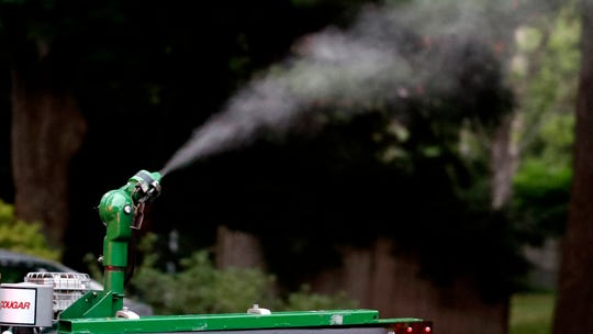 A vapor, sprayed to control mosquitos, hangs airborne as it leaves the nozzle of a East Middlesex Mosquito Control Project pick-up truck on Wednesday, July 8, 2020, while driving through a neighborhood in Burlington, Mass.