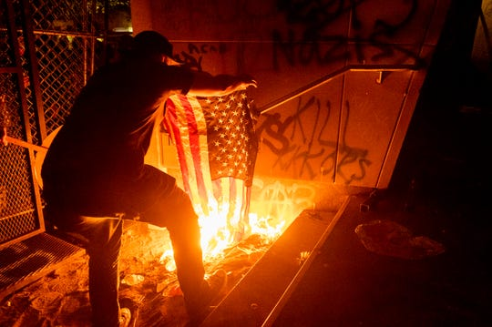 A protester burns an American flag outside the Mark O. Hatfield United States Courthouse on Monday in Portland, Ore.