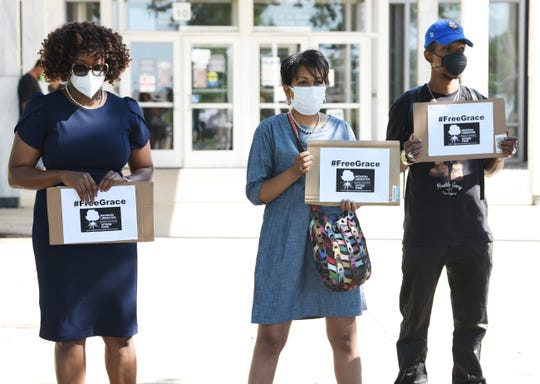 """Tylene Henry, Monique Campbell and Raynard Lanier II hold signs in support for the release of """"Grace"""" from juvenile detention outside a hearing for the girl on Monday, July 20, 2020."""