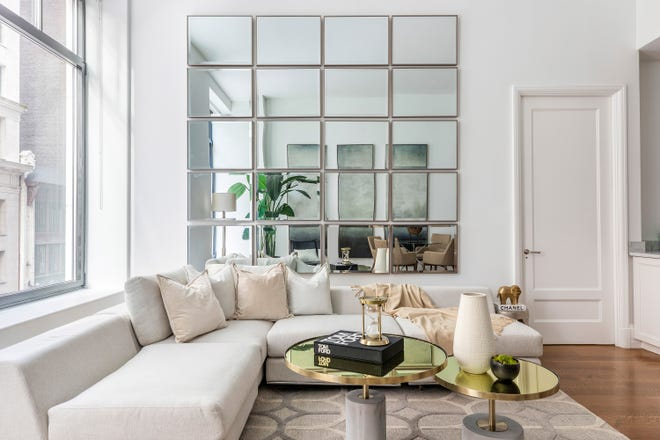 The ceiling line of a living room is heightened using the magic of mirrors.