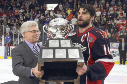 AHL commisioner Dave Andrews, left, presents the Calder Cup to Grand Rapids captain Jeff Hoggan in 2013.