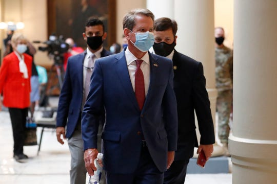Georgia Gov. Brian Kemp returns to his office after giving a coronavirus briefing at the Capitol Friday, July 17, 2020, in Atlanta.