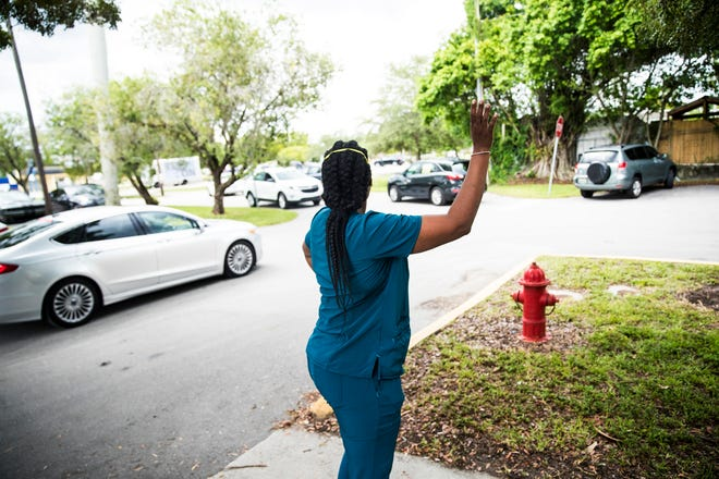 A staff member at Heritage Park Rehabilitation and Healthcare in Fort Myers waves to a   caravan of 1199SEIU United Healthcare Workers East. The union visited three Southwest Florida nursing homes to call for racial justice, present a ÒProtect All WorkersÓ bill of rights, and recognize frontline caregivers during the Covid-19 health crisis. They offered boxed lunches and PPE for staff.