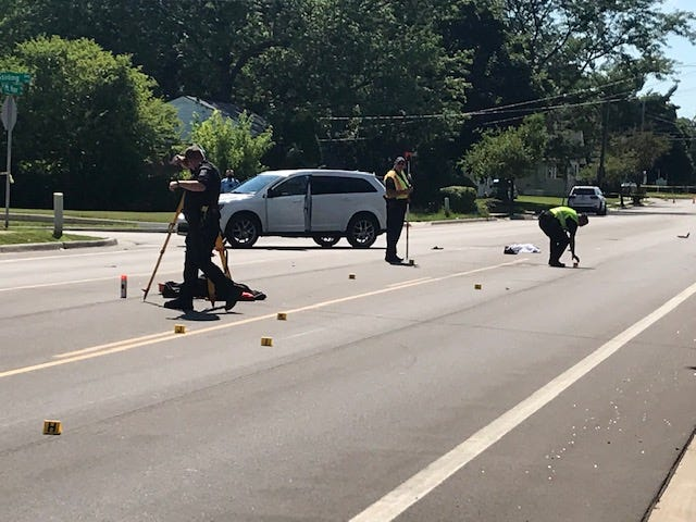 Investigators work at the scene of a crash Friday, July 17, on Mt. Hope Avenue in Lansing.