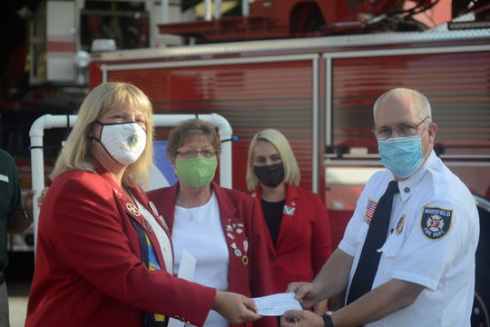 Lions District Governor Kerry Parker, left, hands Mansfield Fire Chief Steve Strickling a check Monday for $3,000.