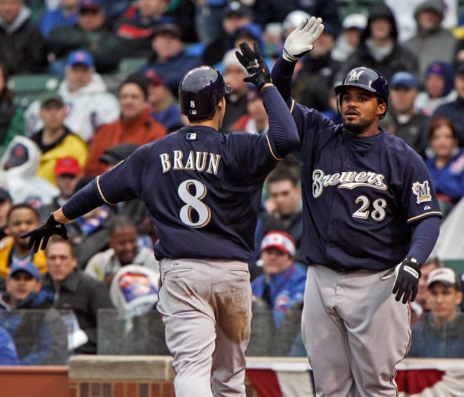 Milwaukee Brewers Ryan Braun and Prince Fielder exchange high-fives after scoring on Corey Hart's double in the ninth inning to send the 2008 season opener against the Chicago Cubs at Wrigley Field into extra innings.