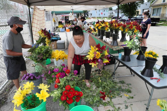 Zongchia Vang, left, and his wife Shoua Vang, right, put together flower displays while their daughter Mai Vang helps customers at rear at the Riverwest farmers market in 2020. This year's Riverwest market opens June 6.