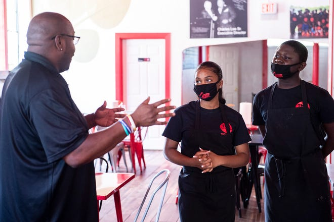 That's My Dog Jr. founder Charles Lee talks with student employees Makhiya Turner and Kenyada Hampton in Montgomery, Ala., on Monday, July 20, 2020.