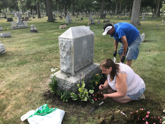 Kandie and Brian Mifflin plant flowers at a grave at Lakeside Cemetery on Sunday, July 19, 2020.
