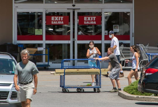 Customers with and without masks intersect at the exit of a home improvement store near York, Pa.