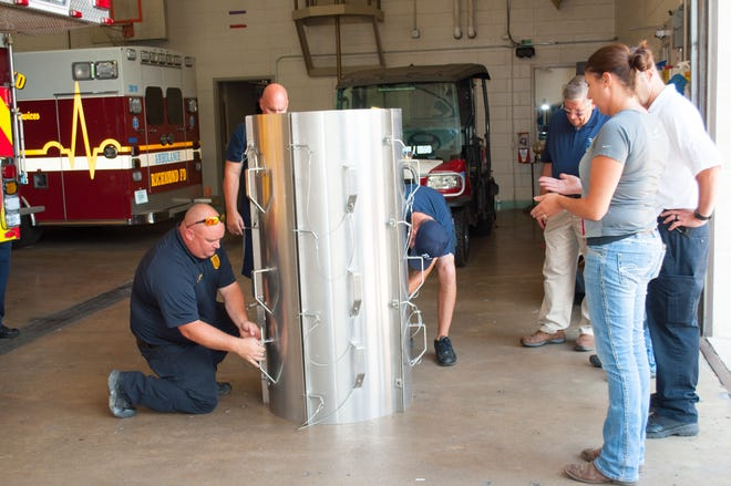 Richmond Fire Department Chief of Training Andrew Buckler (left) and other RFD personnel learn about a grain rescue tube under direction from Nikki Bulach, associate risk manager for Harvest Land Co-op.