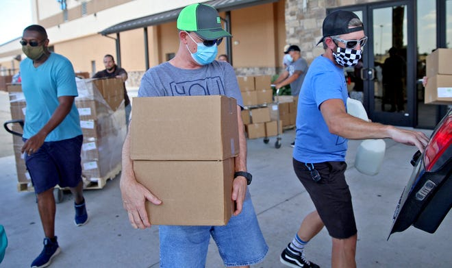 Volunteers at The Life Church in San Angelo load boxes of food into a vehicle during a Farmers to Families food drive Saturday, July 18, 2020.