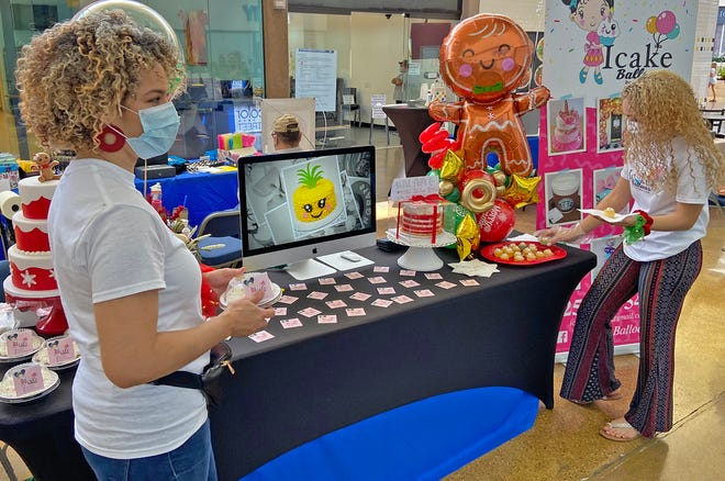 Ivelisse De Jesus, left, and Lydelix De Jesus, right, prepare their booth for customers during the Christmas in July event at the Sunset Mall on Saturday, July 18, 2020.