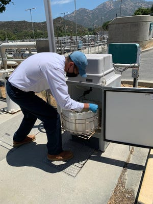 Matthew Reese, a laboratory assistant for the Las Virgenes Municipal Water District takes a sample at the Tapia Water Reclamation Facility. The district has been sending samples to researchers for the purpose of gathering coronavirus data.
