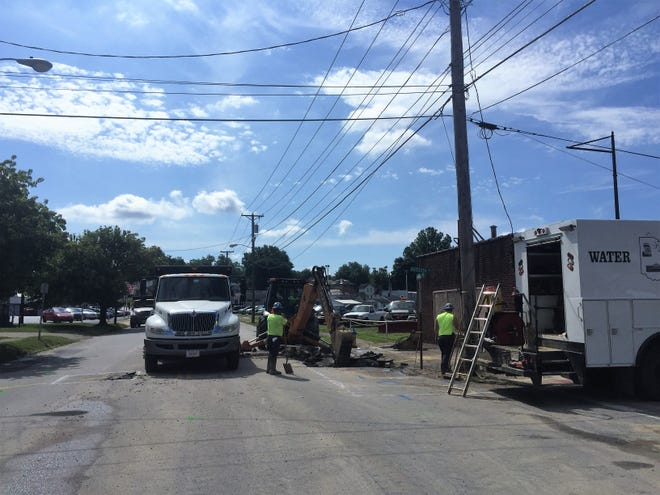 Crews with the City of Zanesville work to repair a water main break on West Main Street on Monday.