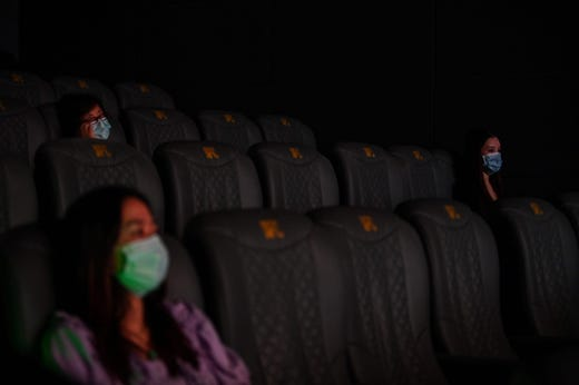 People wearing face masks watch a movie during the first day of re-opening the theaters after COVID-19 in Shanghai on July 20, 2020. - Hundreds of cinemas reopened in scores of Chinese cities on July 20 following a nearly six-month nationwide shutdown due to the coronavirus. But the threat from COVID-19 remains in the air, with cinemas in Beijing still closed for now.