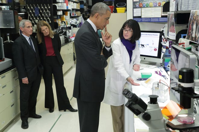 President Barack Obama learns about the results of the experimental Ebola vaccine, which just completed Phase 1 clinical trials, from Dr. Nancy Sullivan, Chief of the National Institute of Allergy and Infectious Diseases Vaccine Research Center Biodefense Research Section. HHS Secretary Sylvia Burwell and NIAID Director Dr. Anthony Fauci accompanied the tour.
