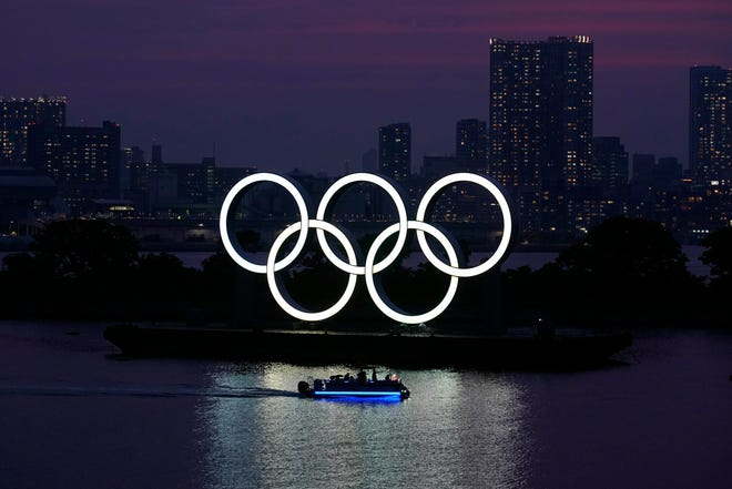 The Olympic rings float in the water at sunset in the Odaiba section in Tokyo on June 3, 2020.