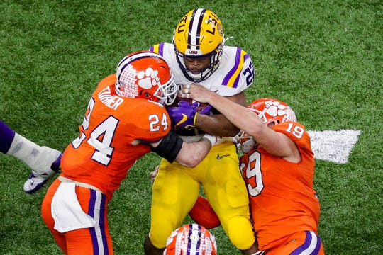 Clemson and LSU, shown during the College Football Playoff national championship, have had at least two dozen athletes and staff test positive for coronavirus since players reported to camp last month.