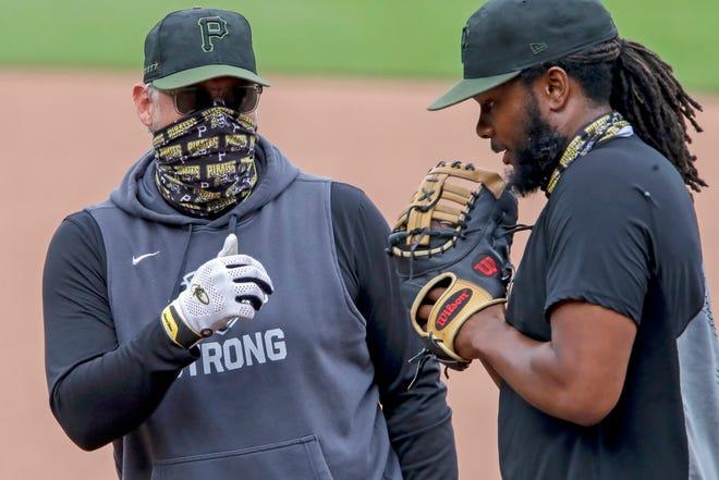 Pirates manager Derek Shelton talks to first baseman Josh Bell.
